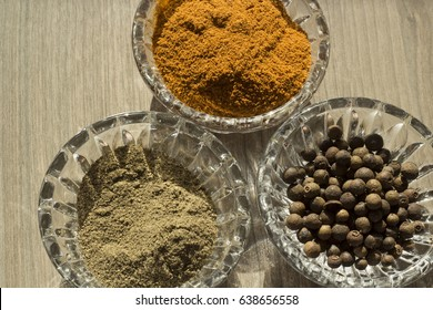 Ground and whole red and black pepper is poured into small transparent saucers