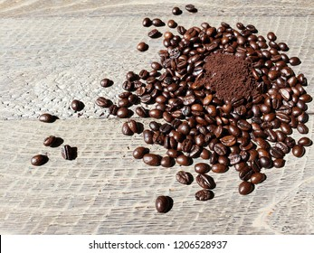 Grounded coffee in centre of Coffee beans on wooden background