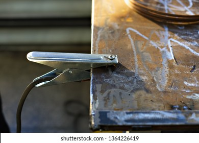 The grounding clamp with the cable from the welding machine is fixed to the metal table on the production.