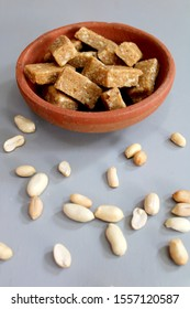 Groundnut chikki famous sweet in south India in a clay bowl surrounded by fried groundnuts