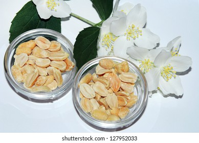 Groundnut in a glass bowl over white background. As ingredient for healthy cookies