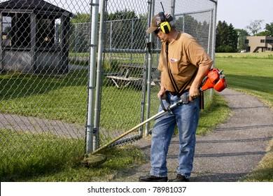 grounds keeper cutting weeds
