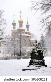 Grounds of Novodevichy convent after snowfall, view of a grave with statue of an angel and Intersession church over Southern Gates (1683-1688) in background  MOSCOW, RUSSIA