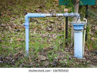 Groundwater well with pvc pipe and system electric deep well submersible pump water on green meadow