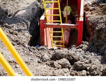 groundworker installing clay drainage pipe while in the trench supported by trench box