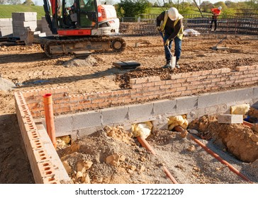 Groundworker is installing internal drainage for a house.