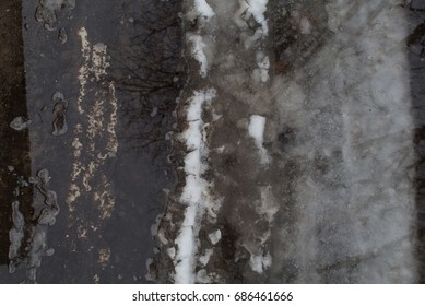 Groung melting snow dark gray puddle footprints