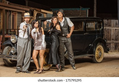 Group of 1920s vintage gangsters outside aiming weapons