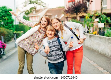 Group of 3 funny kids with backpacks, 2 schoolgirls and one preschooler, back to school concept
