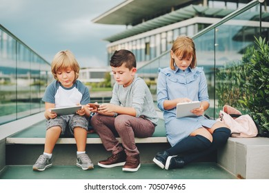 Group of 3 funny kids playing with tablet pc outdoors. Young children using electronic gadgets
