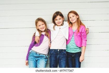 Group of 3 little girls standing outdoors against white wooden background, wearing denim jeans and colorful jackets