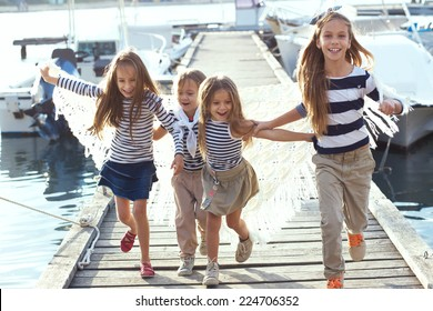 Group of 4 fashion kids wearing same striped navy clothes in marine style running in the sea port