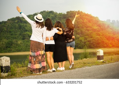 A group of 4 woman friends closely standing with her arms around  each other, watching river and mountain view.