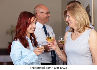 Group of 4 younger and older businesspeople celebrate with wine glasses in their hands