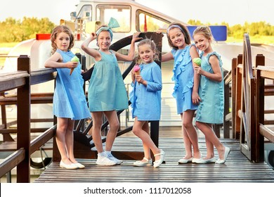 Group 5 five fashion lady kids in elegant striped dresses,marine style. Little girls in designer collection children's clothes. Girlfriends smile,standing on bridge. Vacation,fashionable concept.