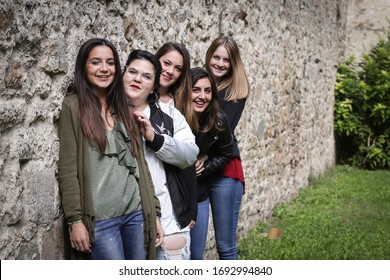 Group of 5 friends having fun outdoors. Stone wall on the background.