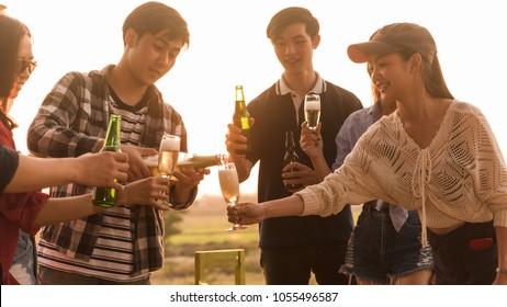 Group of 6 teenager have dinner party celebrating at sunset pouring champange in to glasses
