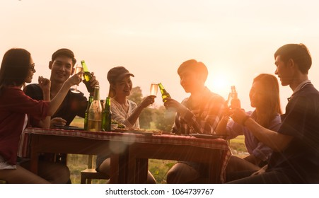Group of 6 teenager have dinner party celebrating at sunset with beautiful landscape background