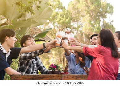 Group of 6 teenagers having fun together without liquor in cafe in afternoon drink milk tea, pink milk and chocolate in plastic glass