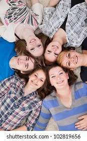 Group of 6 teenagers lying on the floor head next to head, they're looking at camera and smiling