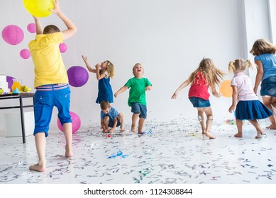 Group of  7 seven children play with air balloons, confetti in l