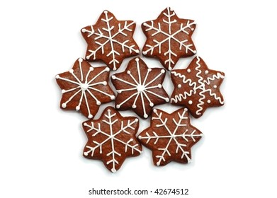 A group of 7 star shaped Christmas decorated sweets (ginger bread) painted with white. Isolated on white