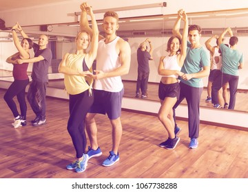Group of active adults dancing salsa together in dance studio and smiling