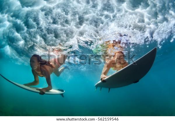 Gruppe von aktiven Mädchen in Aktion. Surfer Frauen mit Surfbrett tauchen unter Wasser unter Brechen große Welle. Gesunder Lebensstil. Wassersport, Extremsurfen im Abenteuerlager bei Familienurlaub im Sommer