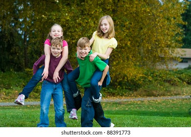 A group of active, healthy children giving each other piggy back rides outside.