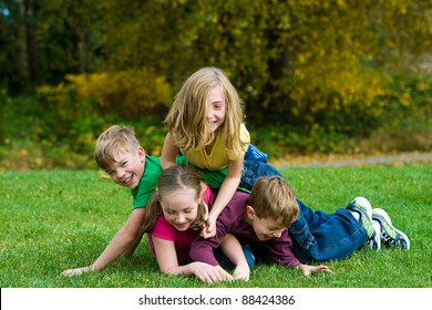 A group of active kids playing in a dog pile on grass.
