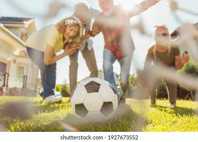 Group of active senior people having fun playing football on the lawn in the backyard, enjoying sunny summer day outdoors, celebrating after scoring a goal