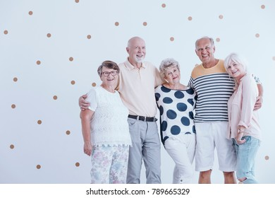 Group of active seniors posing for a photo against white wallpaper with gold dots