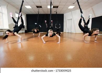 Die Gruppe der aktiven Sportmädchen in schwarzen Sportbekleidung ist im Fitnessraum aktiv. Bungee springt im Fitnessraum