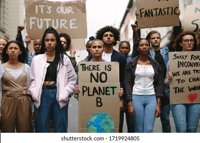 Group of activists with banners protesting to save earth. Men and women rebellions doing a silent protest over global warming and pollution.