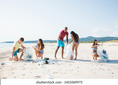 Group of activists friends collecting plastic waste on the beach. People cleaning the beach up, with bags. Concept about environmental conservation and ocean pollution problems