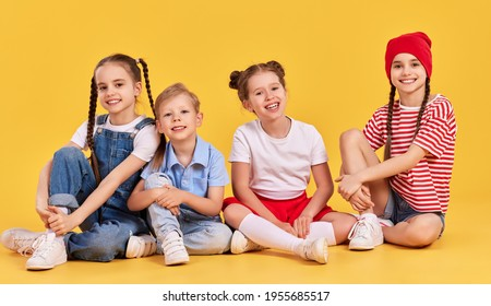 Group of adorable kids in casual outfits and sneakers smiling happily and looking at camera while sitting together against yellow background