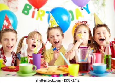 Group of adorable kids having fun by festive table at birthday party