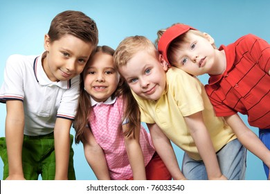 Group of adorable kids looking at camera on blue background