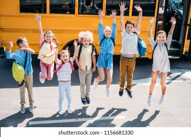 group of adorable schoolchildren jumping in front of school bus and looking at camera