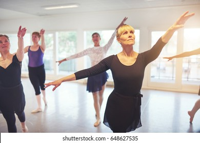 Group of adult ballerinas standing with hands up in class for ballet performing a dance.