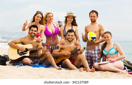 Group of adult friends relaxing on sand at beach with guitar and singing. Selective focus