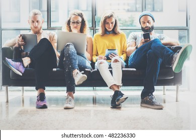 Group Adult Hipsters Friends Sitting Sofa Using Modern Gadgets.Business Startup Friendship Teamwork Concept.Creative People Working Together Marketing Project.Coworking Process Office Studio.Blurred
