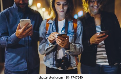 Group adult hipsters using in hands mobile phone closeup, street online wi-fi internet concept, bloggers friends together pointing finger on screen smartphone on background bokeh light in night  city