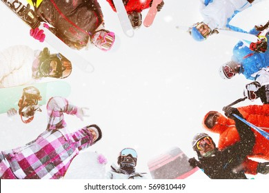 Group of adult men and women stands in circle with ski and snowboard equipment. Winter resort concept. Space for text