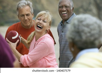 Group of adult multiethnic friends playing American football on the beach