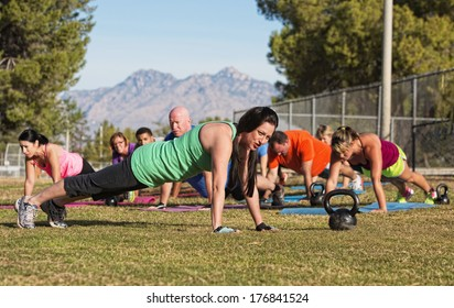 Group of adults doing push up exercises outdoors