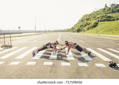 Group of adults performing push up exercise drills at outdoor physical fitness cross-training exercise facility with bright light flare over them