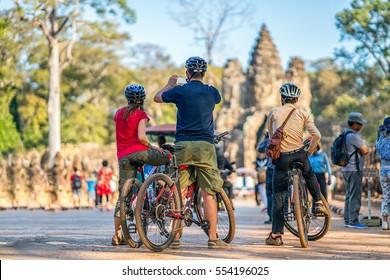 Group of Advanture  travelleres enjoy taking photo at South gate of Angkor Thom, Siem riep, Cambodia