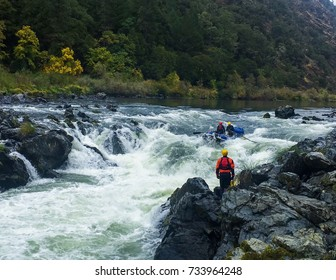 Group of adventure seekers rafting through Rainy Falls, Oregon with spotter watching.