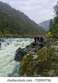 Group of adventure seekers standing on rocky riverbank at Rainy Falls, Oregon.